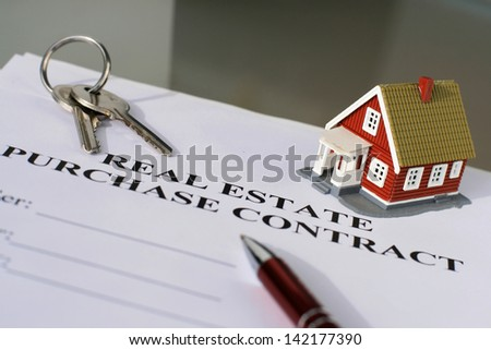Real estate purchase contract on a table. - stock photo
