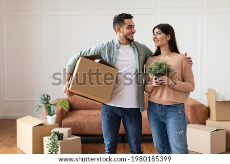 Real Estate Rent, Mortgage And Ownership Concept. Happy Young Man Carrying Cardboard Box And Hugging Woman Who Holding Plant, Relocating To New Apartment Standing At New Home, Free Copy Space Foto stock ©