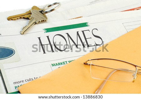 real estate section of the newspaper with yellow envelope, eyeglasses and keys