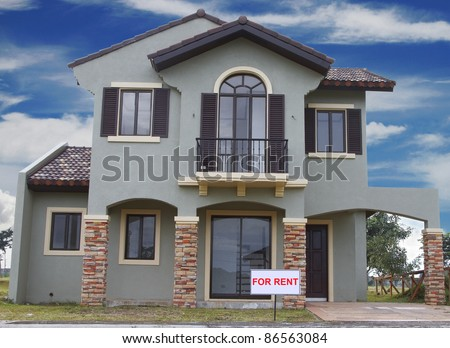 Real estate sign in front of a house for rent with blue clouds.