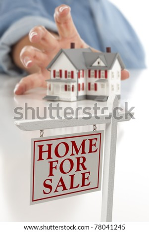 Real Estate Sign in Front of Woman's Hand Reaching for Model House on a White Surface.