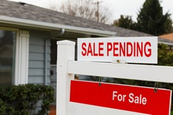 Real estate sign says for sale and pending on the top of it in front of a grey house.