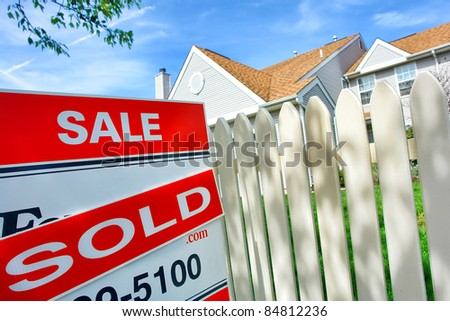 Real estate sold insert on Realtor for sale sign and white picket fence at a selling suburban house after a successful resale brokerage transaction in the residential multiple listing service