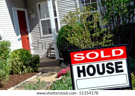 Real estate sold rider insert on a Realtor house for sale sign in the front yard of a resale home under purchase contract