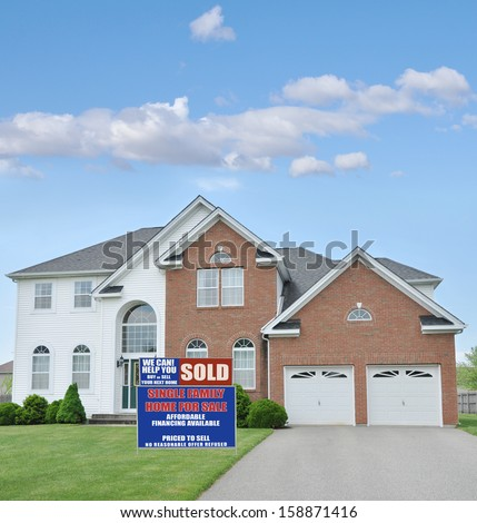 Real Estate Sold Sign Large McMansion Style Brick Home Double Garage Landscaped Front yard Lawn Blue Sky Clouds Residential Neighborhood USA
