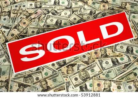 Real estate sold sign over money blanket of assorted dollar bills