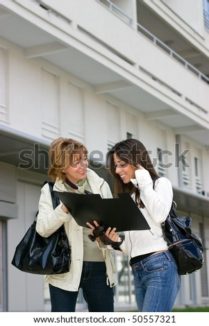 Real Estate woman Agent   with young woman customer standing  in front  of a new building and looking a document