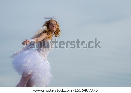 Real fairy from magical stories. Concept of innocent child. A beautiful teen with blonde curly hair and a bow and arrow as cupid - Valentines Day. Angel wings baby #1556489975