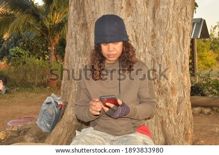 Real farmer thai woman , Asian aged 50 years chatting  the smartphone in hand dressed like a soldier, seating relax on the log and big tree behind. Stock fotó ©