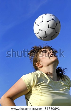 Real female soccer or football player during a match, reaching to hit the ball with her head and score a goal with sky and stadium spot lights in background.