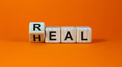 Real heal symbol. Fliped a wooden cube with words 'Real heal'. Beautiful orange background, copy space. Medical and real heal concept.