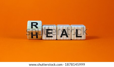Real heal symbol. Fliped a wooden cube with words 'Real heal'. Beautiful orange background, copy space. Medical and real heal concept. ストックフォト ©
