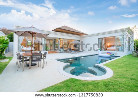 real home or house  Exterior design showing tropical pool villa with greenery garden, sun bed, umbrella, pool towels and colorful floating unicorn