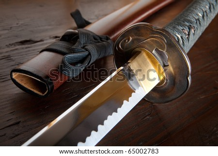 Real japanese samurai sword and sheath on wooden board