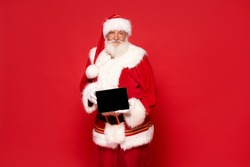 Real jolly Santa Claus holding tablet as a Christmas gift.Red studio background.