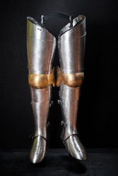 Real knightly armor made of iron for legs on a black background.