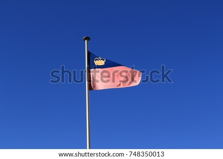 Real Liechtenstein national flag fluttering on a flag pole in wind, isolated on real blue sky background. #748350013