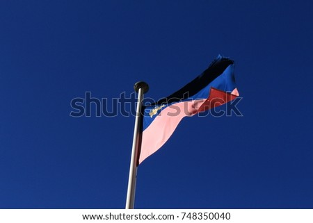Real Liechtenstein national flag fluttering on a flag pole in wind, isolated on real blue sky background. #748350040