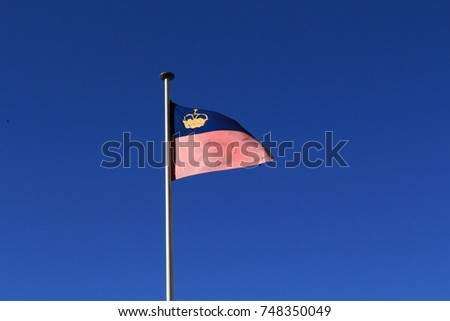 Real Liechtenstein national flag fluttering on a flag pole in wind, isolated on real blue sky background. #748350049