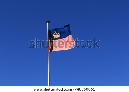 Real Liechtenstein national flag fluttering on a flag pole in wind, isolated on real blue sky background. #748350061