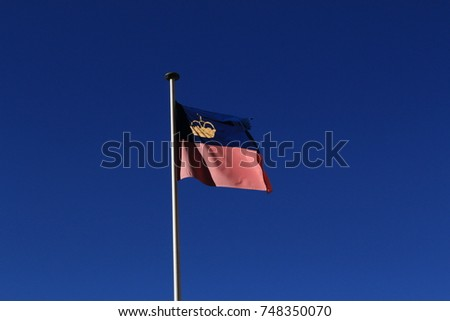Real Liechtenstein national flag fluttering on a flag pole in wind, isolated on real blue sky background. #748350070