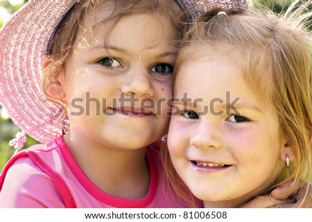 Real life cousins, two happy little girls hugging outside on a beautiful sunny day, best friends forever.