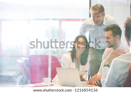 Real life small business meeting with four attractive business people. This is a typical workspace environment where the senior employee is mentoring their younger workers.