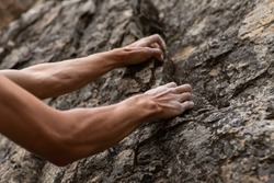 Real life struggle concept as a man attempts to climb a steep rock face. Low angle view of arms struggling to find good grip positions. Copy space to right