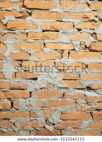 Real loft wall of red bricks decorated with white paint under hard vertical light. Vertical background.