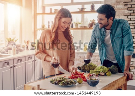 Real love. Beautiful young couple cooking dinner and drinking wine while standing in the kitchen at home
