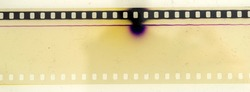 real macro photo of overexposed 35mm cine film strip with dust and nice details on white background.