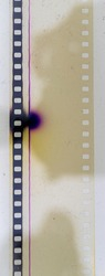 real macro photo of overexposed 35mm cine film strip with dust and nice details under glass surface on white background.