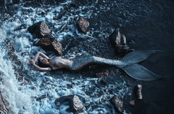 real mermaid posing relax resting ocean shore. Silver tail seductive body covered scales fashion model. Stylish idea summer photo shoot. fabulous mistress queen of  sea storm. chic wet long black hair
