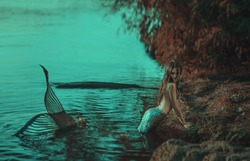 real mermaid posing relax resting ocean shore. Silver tail seductive body covered scales fashion model. Stylish idea autumn photo shoot. fabulous mistress queen of  sea storm. chic wet long black hair