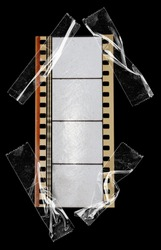 real 35mm cine phono film strip with empty cells or frames isolated on black backgroud with cool texture and optical stereo sound, analog soundfilm or movietone fixed by sticky tape, macro photo.