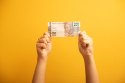 Real, money from Brazil. Dinheiro, Brasil, Reais. A banknote of two hundred reais. hand on yellow background holding Brazilian money, two hundred reais bill