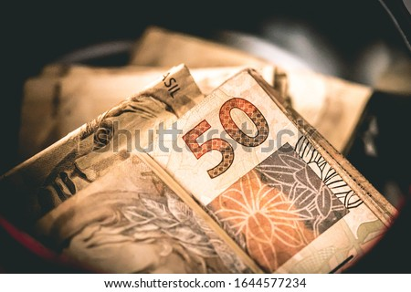 Real, Money from Brazil. Dinheiro, Brasil, Reais, Real Brasileiro. A Real banknotes inside money box.