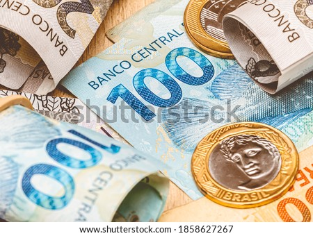 Real, money from Brazil. Dinheiro, Reais, Brasil, Real Brasileiro. A group of brazilian banknotes and coins on a desk.  Foto stock ©