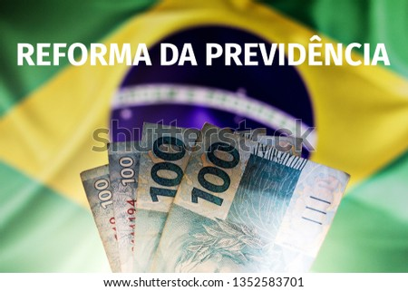 """Real notes, Brazilian money with Brazilian flag, blurred in the background. Text written above """"Reform of Social Security"""", in Portuguese. #1352583701"""