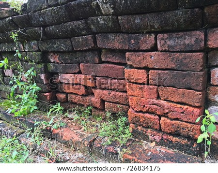 Real old red brick wall texture background interior with small plant at archaeological site in Wat Khao Suwan Khiri temple, Ratchaburi, Thailand