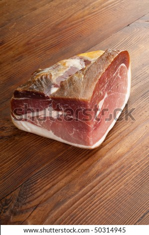 real parma ham over ancient wood table vertical shoot