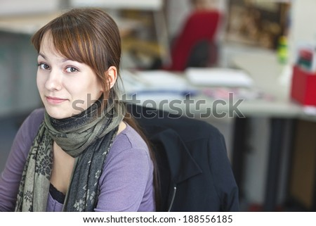 Real People - Portrait of a smart and handsome young woman in office with available light
