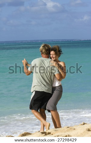 Real people. Real love. Romantic couple dancing salsa on blue Caribbean sea background.