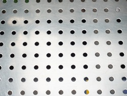 Real perforated stainless metal sheet in construction. Perforated metal sheet. Metal mesh with round holes.