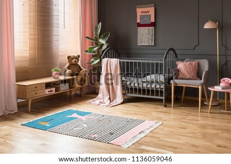 Real photo of a baby crib standing between a low cupboard and an armchair, lamp and stool in child's room interior with wooden floor and grey walls with molding