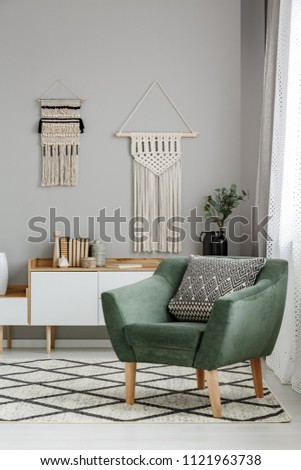 Real photo of a boho living room interior with macrame hanging on gray wall behind a comfy, green armchair with a cushion #1121963738
