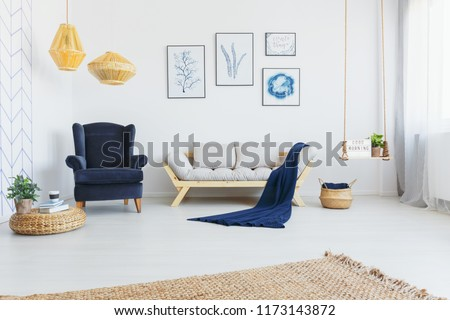 Real photo of a bright living room interior with a comfy armchair, sofa, wicker lamps and botanical graphics on the wall #1173143872