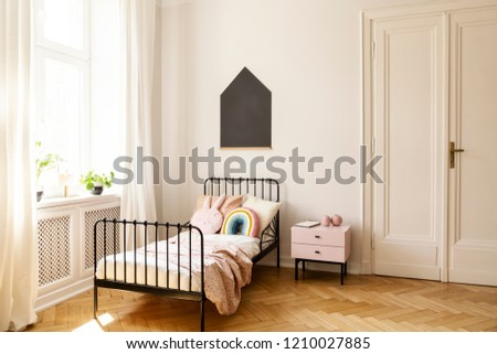 Real photo of a child bedroom interior with a single bed, bedside table, window and blackboard on a wall