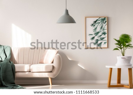 Real photo of a couch with blanket and pillow standing next to a table with plant in a beige living room interior with a hanging lamp and poster on the wall