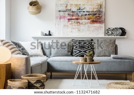 Real photo of a cozy couch with cushions standing behind a small table and in front of a shelf with a painting in boho living room interior with baskets and white rug #1132471682